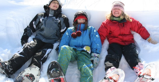 Kids take a break from snowshoeing.